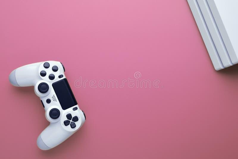 Concepto del juego Juego del ordenador Palanca de mando y Conor blancos de la consola del gamepad en fondo rosado imagen de archivo
