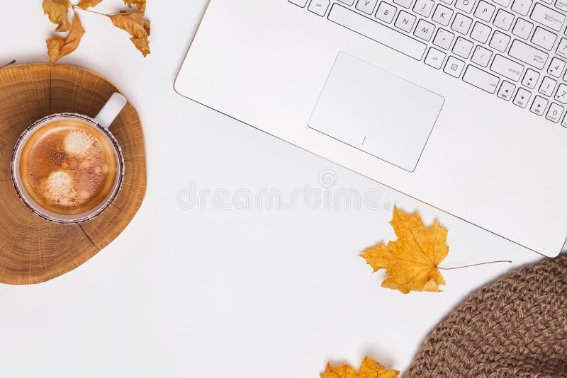 Concepto del lugar de trabajo del otoño con café y hojas amarillas imagenes de archivo