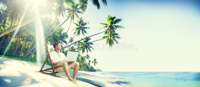 Concepto del mar del verano de la playa del ordenador portátil del hombre imagen de archivo libre de regalías