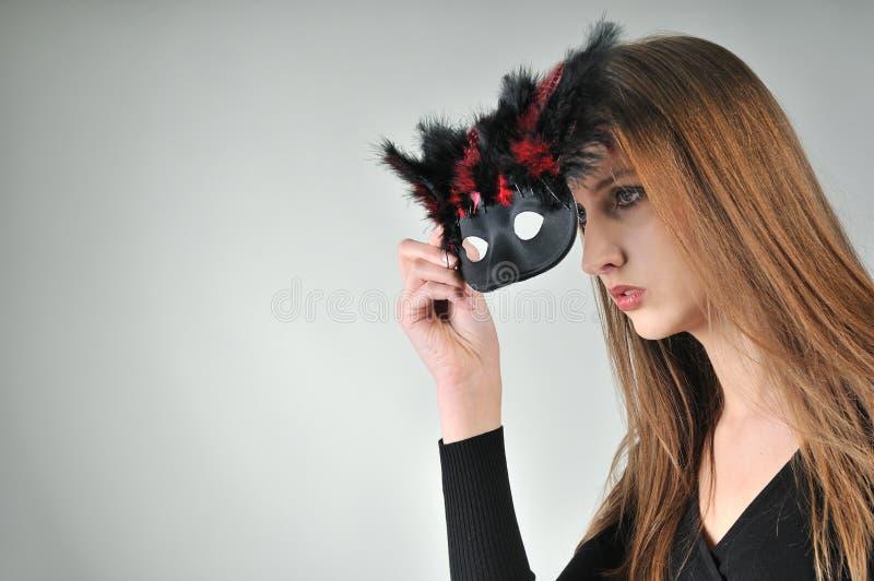 Concepto del misterio - mujer en máscara fotografía de archivo