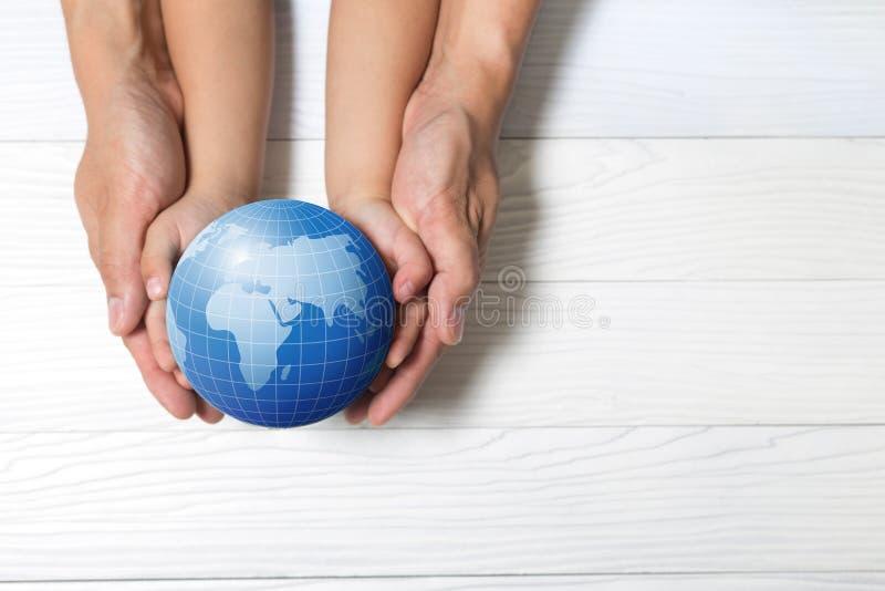 Concepto del mundo: Dos manos humanas que se consideran globales en backgrou de madera fotos de archivo libres de regalías