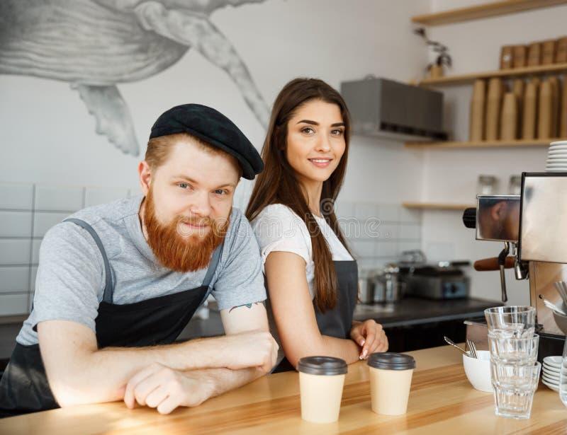 Concepto del negocio del café - hombre barbudo joven positivo y par atractivo hermoso del barista de la señora en el delantal que imagen de archivo