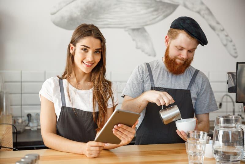 Concepto del negocio del café - propietarios de negocio jovenes felices de los pares de la pequeña cafetería que trabajan y que a fotos de archivo libres de regalías
