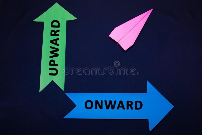 Concepto del negocio con las flechas planas y coloreadas de papel en fondo azul marino Hacia arriba, hacia adelante foto de archivo libre de regalías