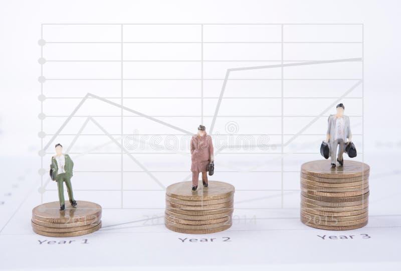 Concepto del negocio con los trabajadores miniatura de la gente en moneda del dinero imagen de archivo libre de regalías