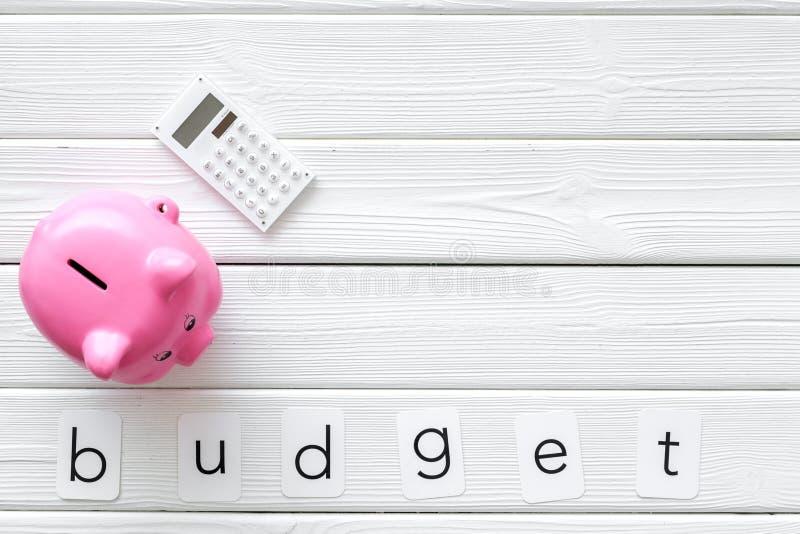 Concepto del negocio con palabra, la hucha y la calculadora del presupuesto en el espacio de madera blanco de la opinión de top d foto de archivo