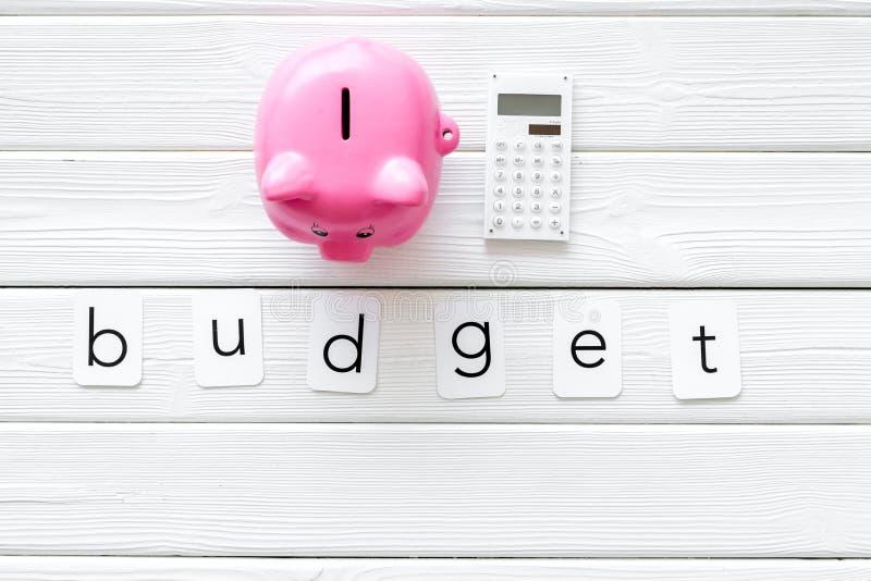 Concepto del negocio con palabra, la hucha y la calculadora del presupuesto en la opinión de top de madera blanca del fondo fotografía de archivo libre de regalías