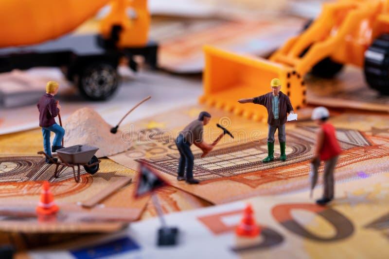 Concepto del negocio de construcción - los trabajadores combinan el trabajo difícilmente para ganar más dinero imágenes de archivo libres de regalías