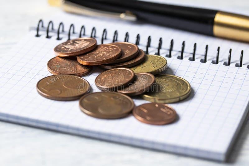 Concepto del negocio, de las finanzas o de la inversión Monedas, talonario de cheques o cuaderno y pluma Fondo de madera blanco fotos de archivo