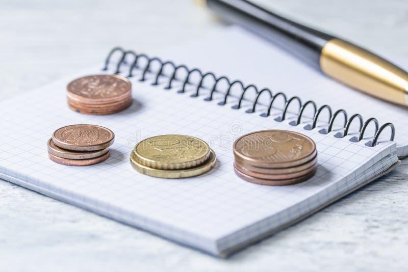 Concepto del negocio, de las finanzas o de la inversión Monedas, talonario de cheques o cuaderno y pluma Fondo de madera blanco imagen de archivo