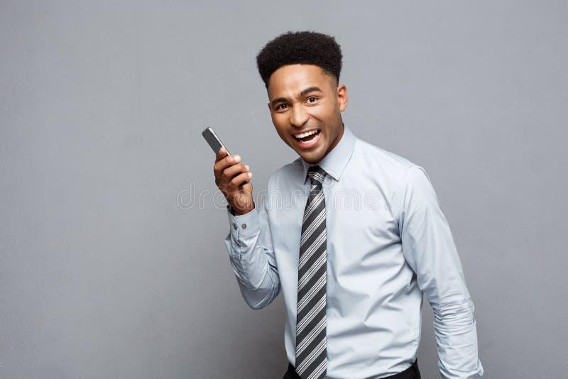 Concepto del negocio - el hablar feliz del hombre de negocios afroamericano profesional alegre en el teléfono móvil con el client imagen de archivo libre de regalías
