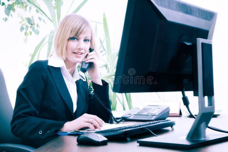Concepto del negocio - empresaria rubia que habla en el teléfono mientras que trabaja en el ordenador en la oficina fotografía de archivo