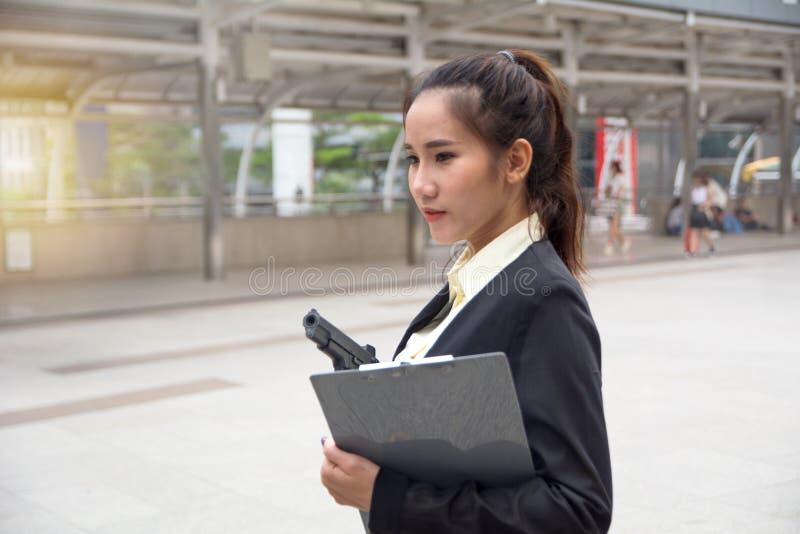 Concepto del negocio ese un escolta de sexo femenino que sostiene el arma disponible imagen de archivo libre de regalías