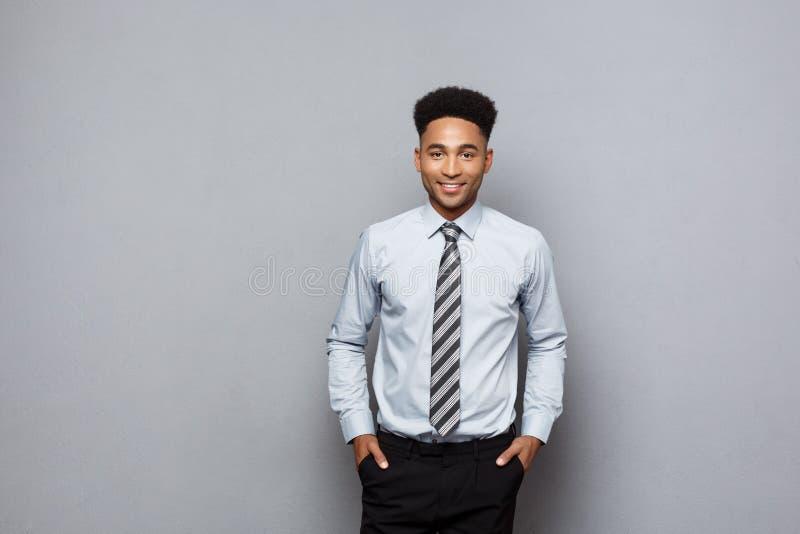 Concepto del negocio - hombre de negocios afroamericano profesional confiado feliz que presenta sobre fondo gris imagen de archivo