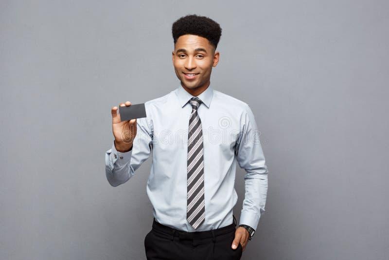 Concepto del negocio - hombre de negocios afroamericano profesional hermoso feliz que muestra la tarjeta de presentación al clien fotos de archivo