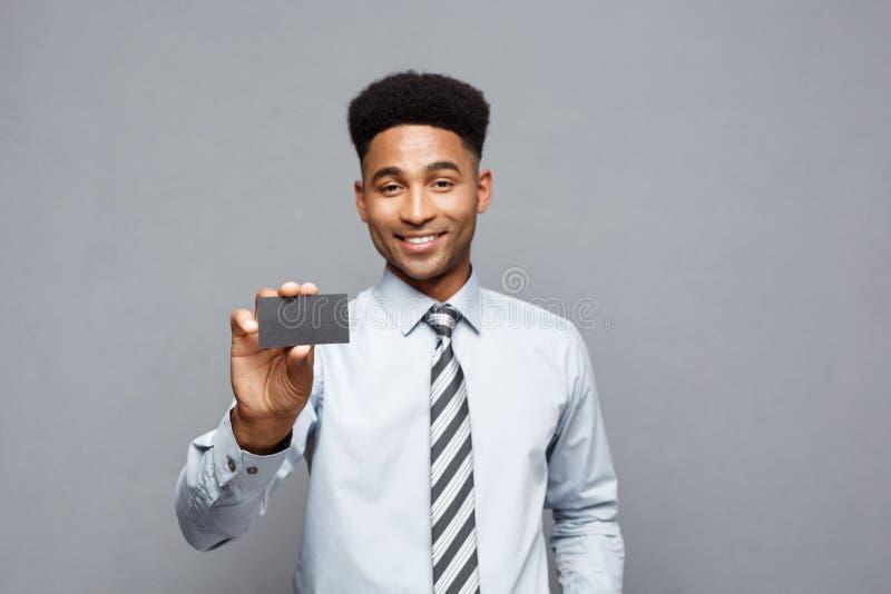Concepto del negocio - hombre de negocios afroamericano profesional hermoso feliz que muestra la tarjeta de presentación al clien imagen de archivo