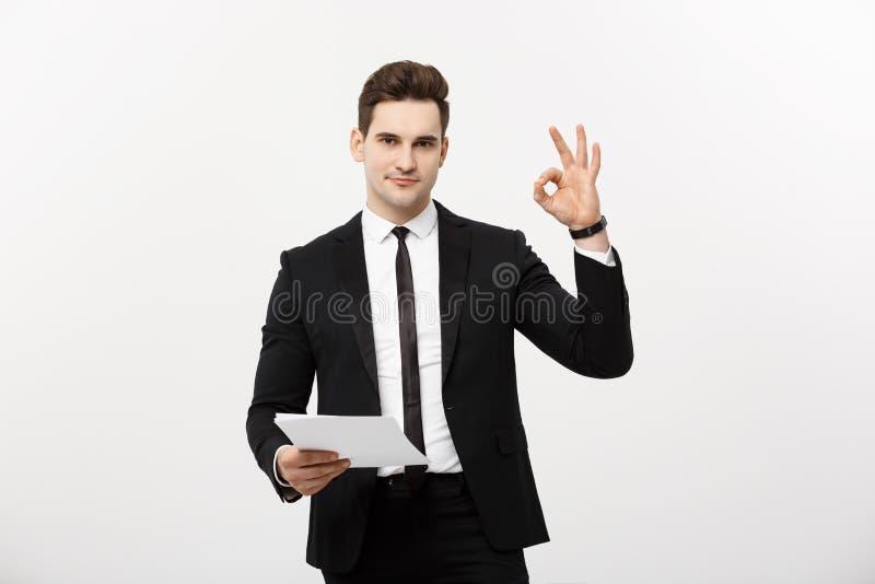 Concepto del negocio: Hombre de negocios atractivo del retrato que trabaja en informe y que muestra la muestra aceptable del fing imágenes de archivo libres de regalías
