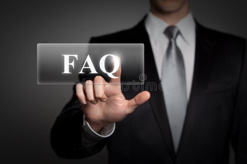 Concepto del negocio - hombre de negocios presiona el botón virtual de la pantalla táctil - palabra inglesa FAQ fotografía de archivo libre de regalías