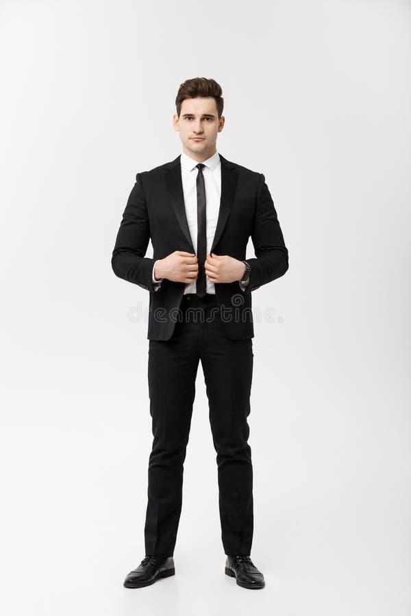 Concepto del negocio: Individuo hermoso joven de la sonrisa feliz hermosa del hombre en el traje elegante que presenta sobre Grey imagen de archivo libre de regalías