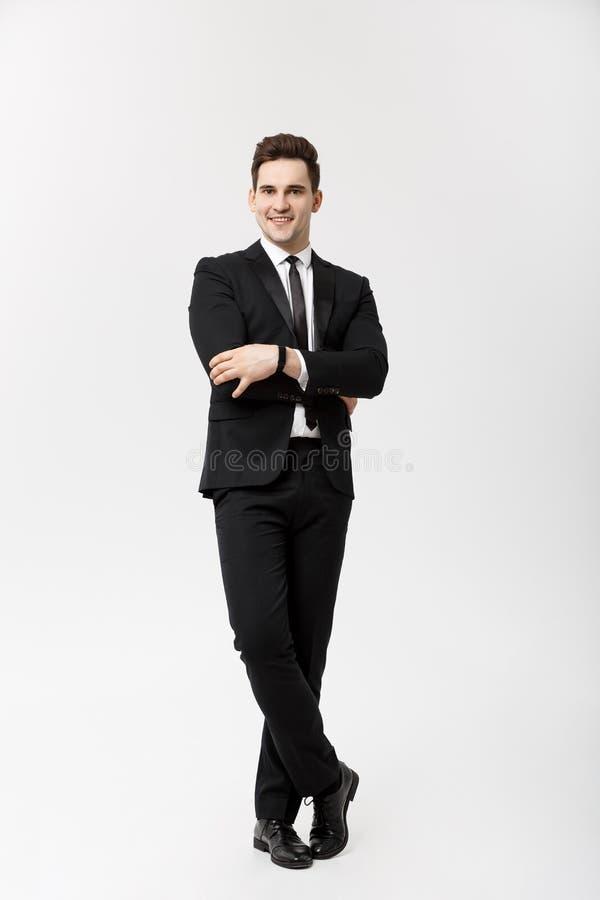 Concepto del negocio: Individuo hermoso joven de la sonrisa feliz hermosa del hombre en el traje elegante que presenta sobre Grey fotos de archivo