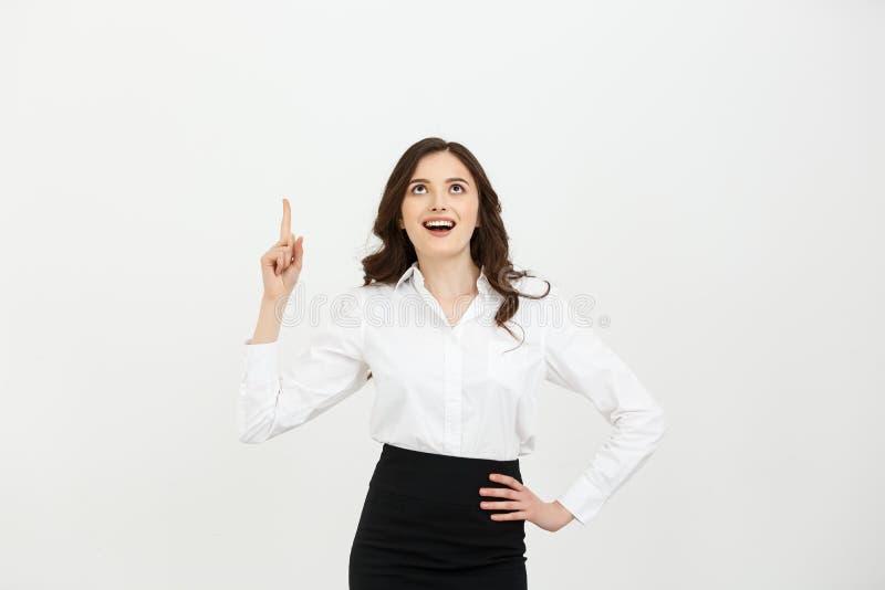 Concepto del negocio: Muchacha caucásica joven atractiva abierta su boca y señalar su dedo índice al top Ella mira fotografía de archivo libre de regalías