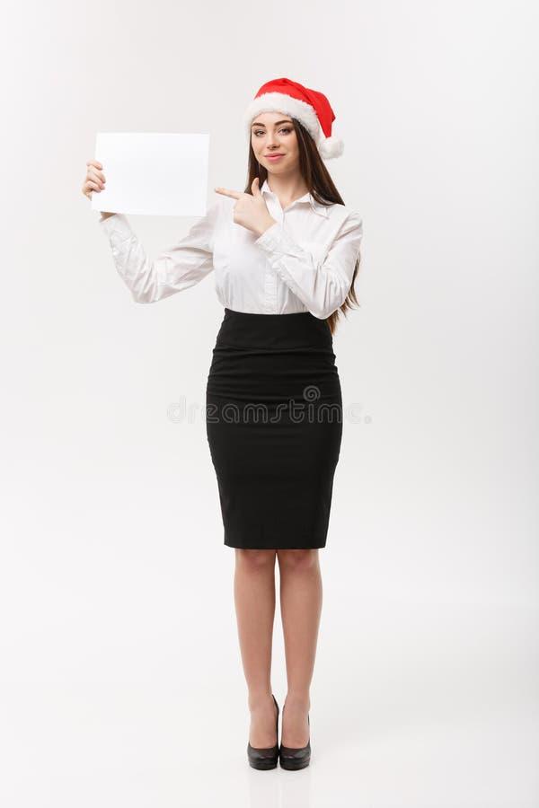 Concepto del negocio - mujer de negocios caucásica joven hermosa con el sombrero de santa que señala al papel en blanco usando pa imagen de archivo libre de regalías