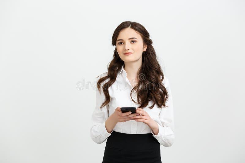 Concepto del negocio: Retrato de la mujer de negocios que usa un teléfono móvil aislado en un fondo blanco imagenes de archivo