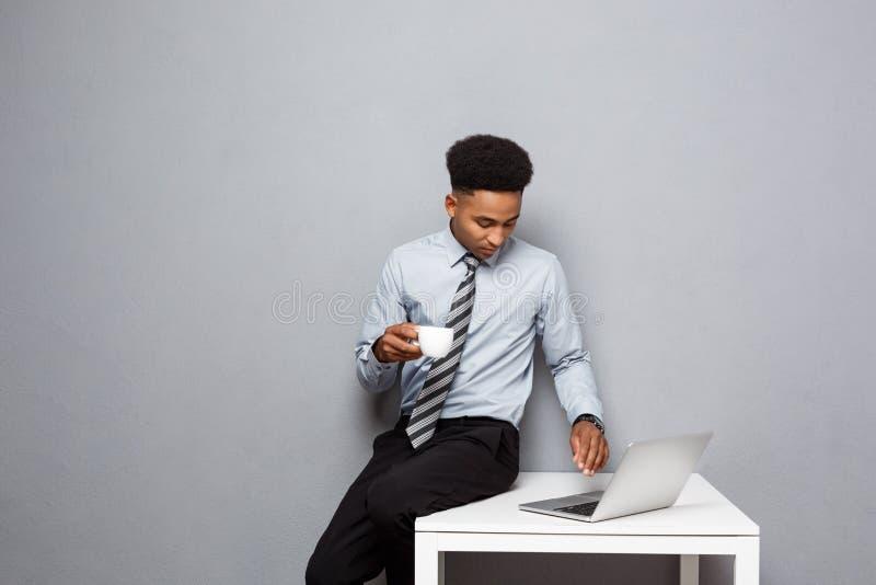 Concepto del negocio - retrato del hombre de negocios afroamericano que come el café que se sienta en un escritorio usando un ord foto de archivo