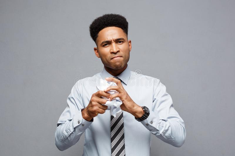 Concepto del negocio - retrato del hombre de negocios afroamericano serio que celebra el arrugamiento de los papeles del informe  foto de archivo