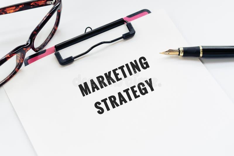 Concepto del negocio, tablero con estrategia de marketing de la palabra, pluma y vidrios en el fondo blanco fotografía de archivo