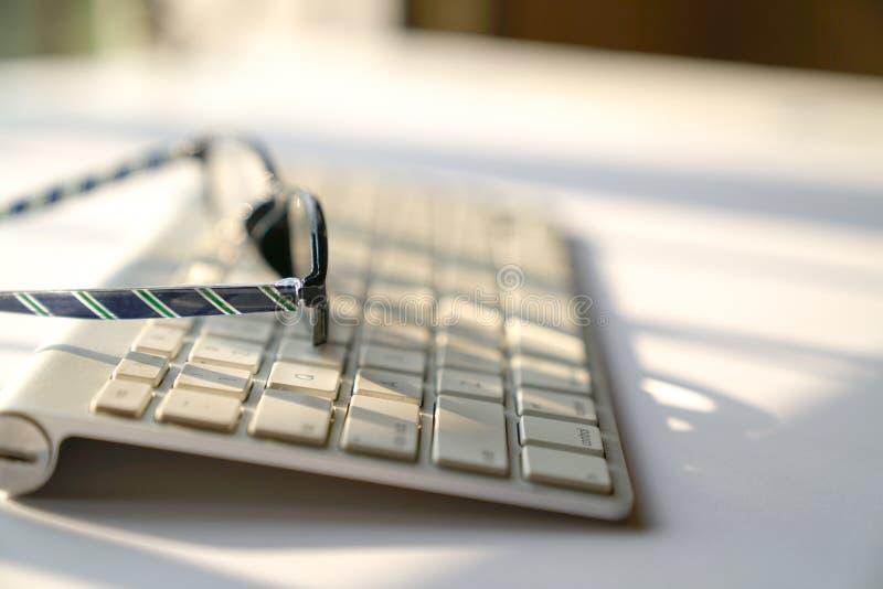 Concepto del negocio: teclado y vidrios de lectura en el fondo blanco fotografía de archivo