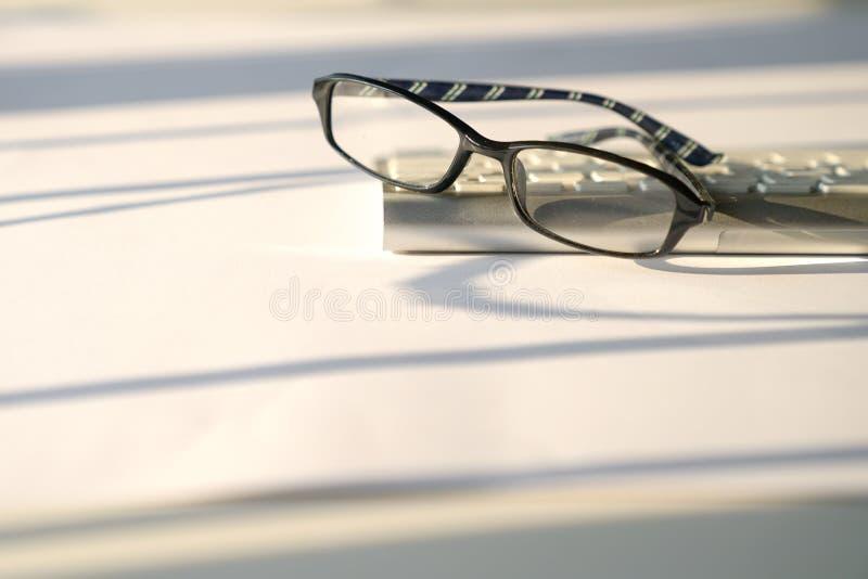 Concepto del negocio: teclado y vidrios de lectura en el fondo blanco imagen de archivo