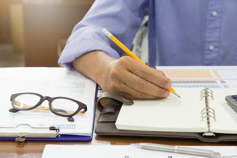 Concepto del negocio y de las finanzas del funcionamiento de la oficina, escritura del hombre de negocios en un cuaderno con la p imágenes de archivo libres de regalías