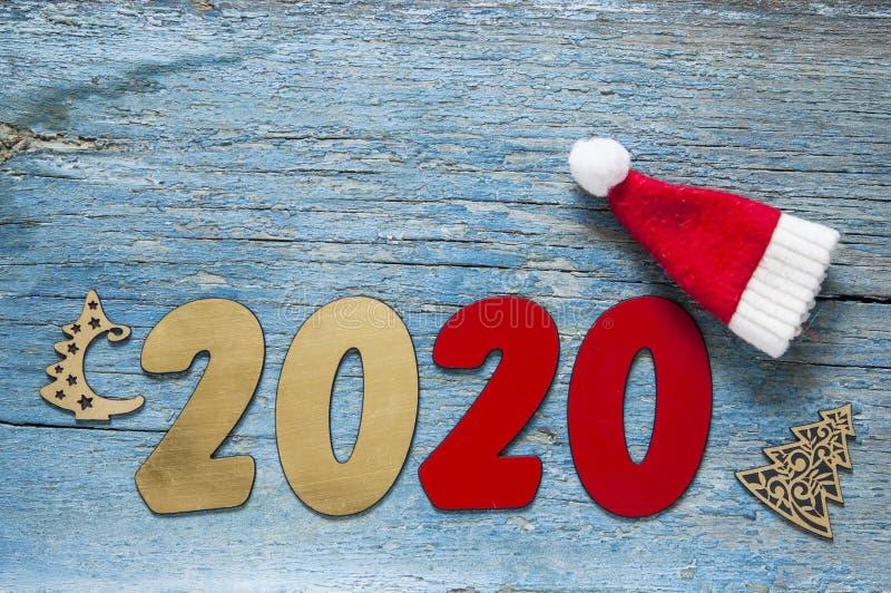 Concepto del A?o Nuevo Dígitos 2020 en fondo de madera con la decoración de la Navidad imagenes de archivo