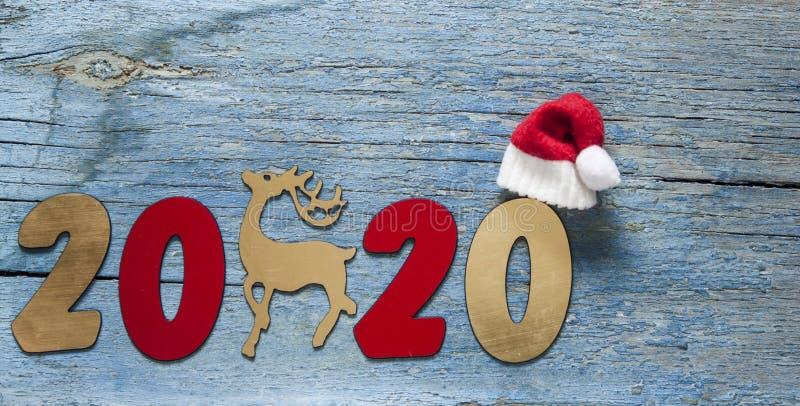 Concepto del A?o Nuevo Dígitos 2020 en fondo de madera con la decoración de la Navidad foto de archivo