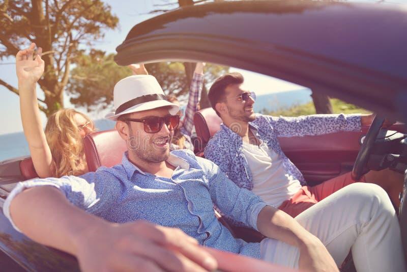 Concepto del ocio, del viaje por carretera, del viaje y de la gente - amigos felices que conducen en coche del cabriolé a lo larg fotos de archivo libres de regalías