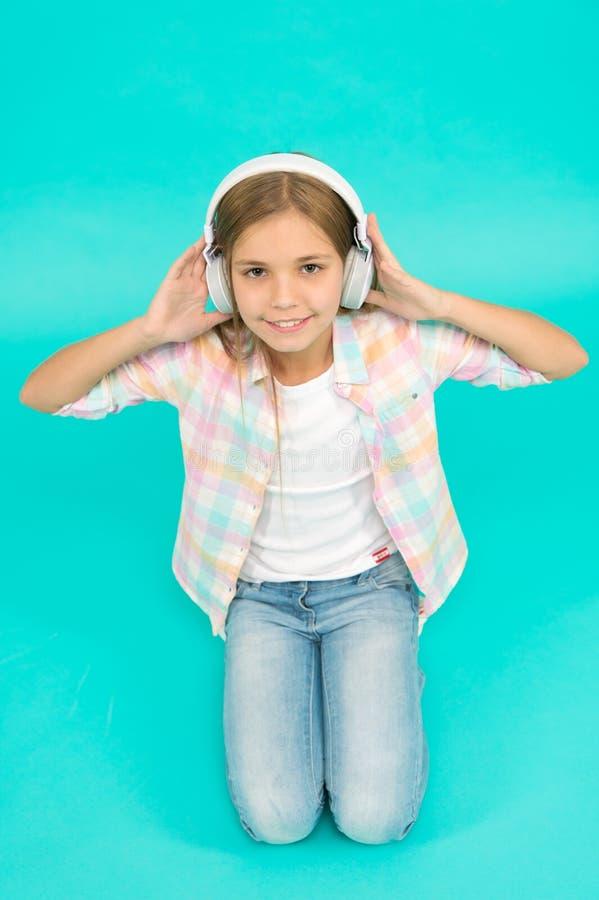 Concepto del ocio La niña escucha los auriculares de la canción Goce de la pista de la banda preferida Niño de la muchacha escuch fotografía de archivo