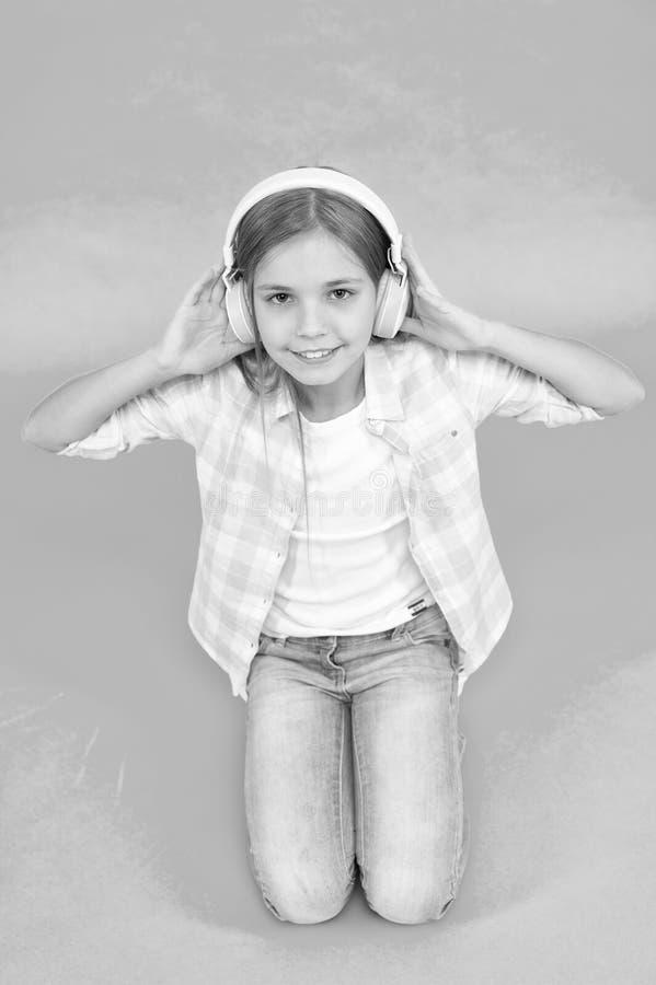 Concepto del ocio La ni?a escucha los auriculares de la canci?n Goce de la pista de la banda preferida Ni?o de la muchacha escuch imágenes de archivo libres de regalías