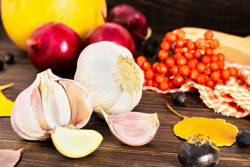 Concepto del otoño con ajo y calabazas, cebollas rojas, serbal, escaramujo y hojas de otoño producidos en fondo de madera imagen de archivo libre de regalías
