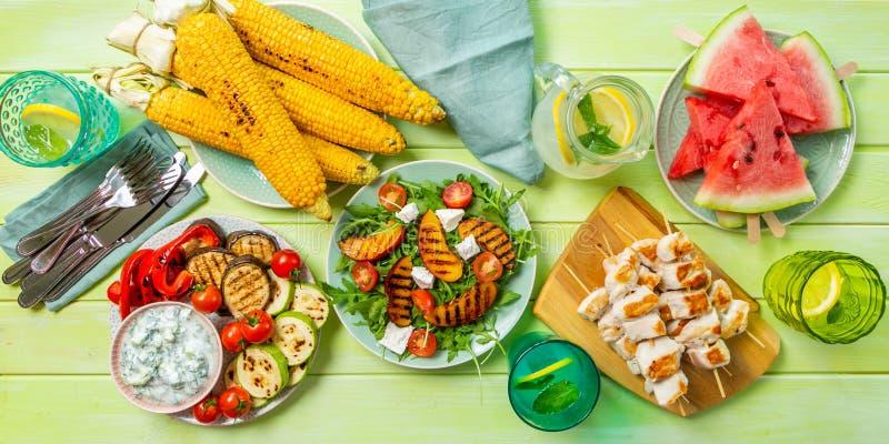 Concepto del partido del Bbq del verano - pollo asado a la parrilla, verduras, maíz, ensalada, visión superior foto de archivo