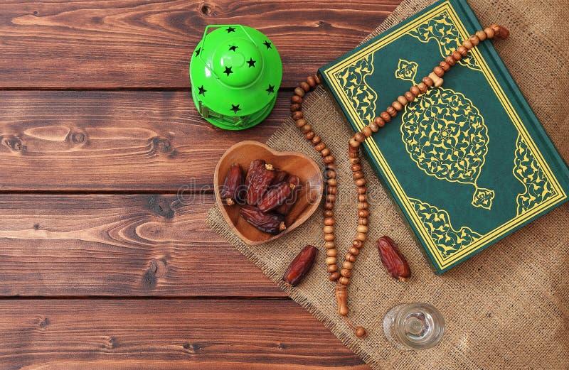 Concepto del partido iftar del Ramadán Gotas islámicas del Quran y del rosario del libro sagrado con las fechas deliciosas, higos imágenes de archivo libres de regalías