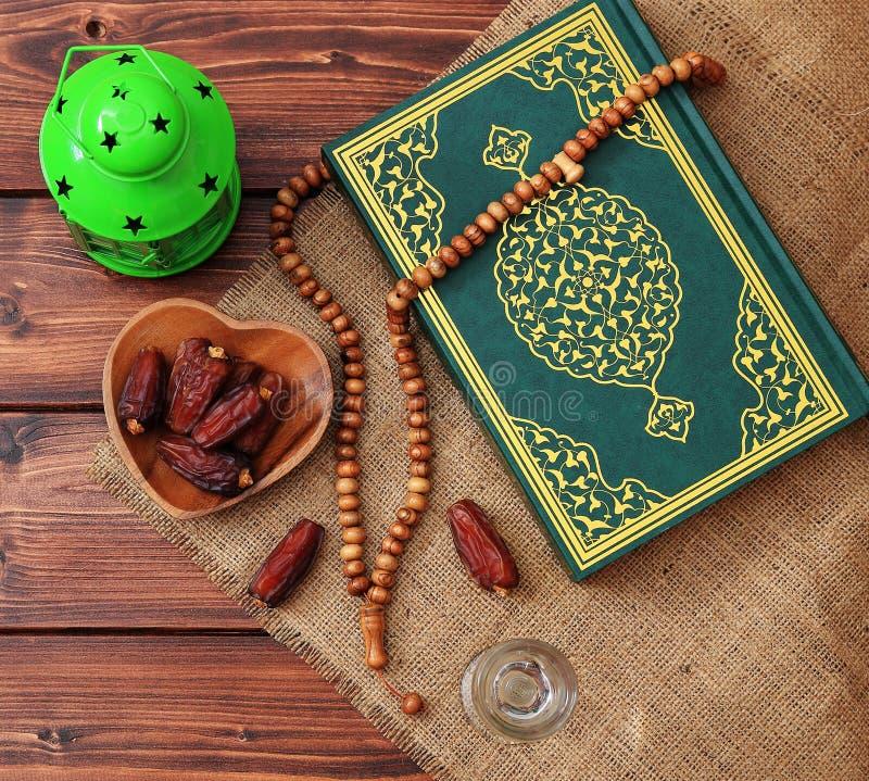 Concepto del partido iftar del Ramad?n Gotas isl?micas del Quran y del rosario del libro sagrado con las fechas deliciosas, higos imagenes de archivo