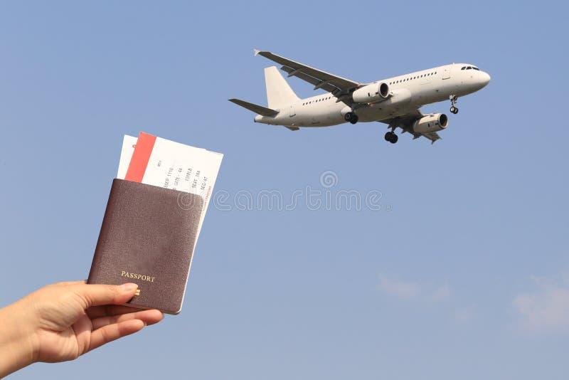 Concepto del planeamiento del viaje, pasaporte de la tenencia de la mano y billetes de avión con el aeroplano en fondo del cielo  imagenes de archivo