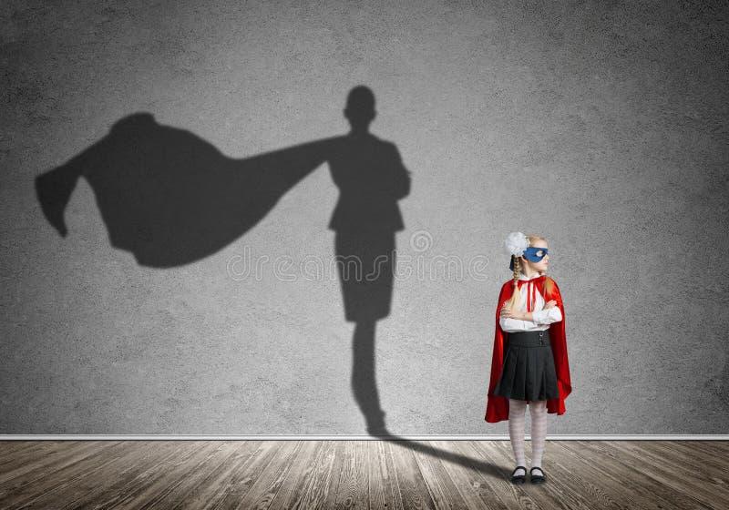 Concepto del poder de la muchacha con el guarda y la sombra lindos del niño en la pared Técnicas mixtas foto de archivo libre de regalías