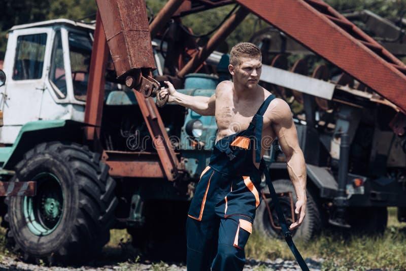 Concepto del poder Tractor del tirón del hombre del poder con la grúa Levantador del poder en el emplazamiento de la obra Sienta  foto de archivo
