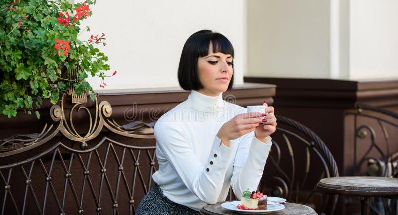 Concepto del postre Tiempo y relajación agradables Bocado delicioso y gastrónomo La muchacha relaja el café con café y el postre foto de archivo