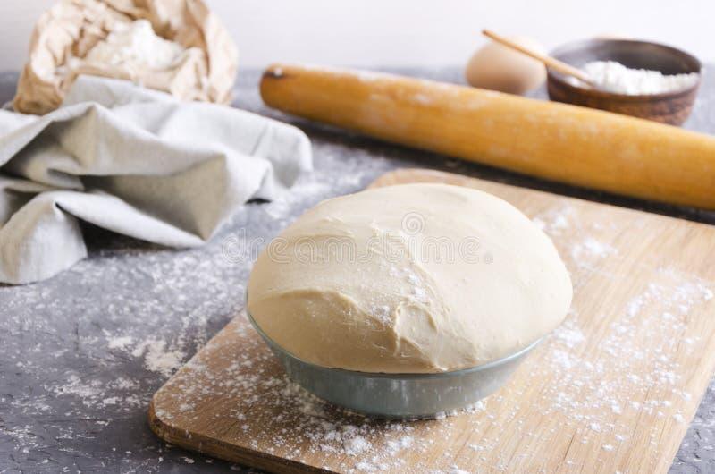 Concepto del proceso de panader?a Primer de la pasta fresca en el cuenco en la tabla de cortar de madera, diversos ingredientes p fotos de archivo libres de regalías