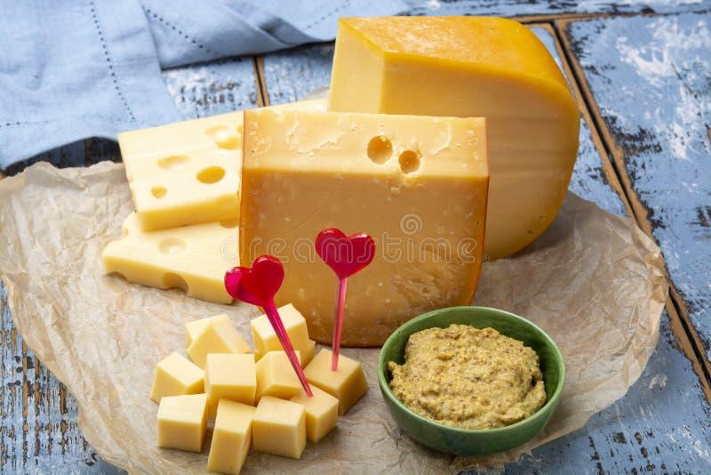 Concepto del queso de Holanda del amor, bloques de queso duro joven y envejecido del Gouda imagenes de archivo