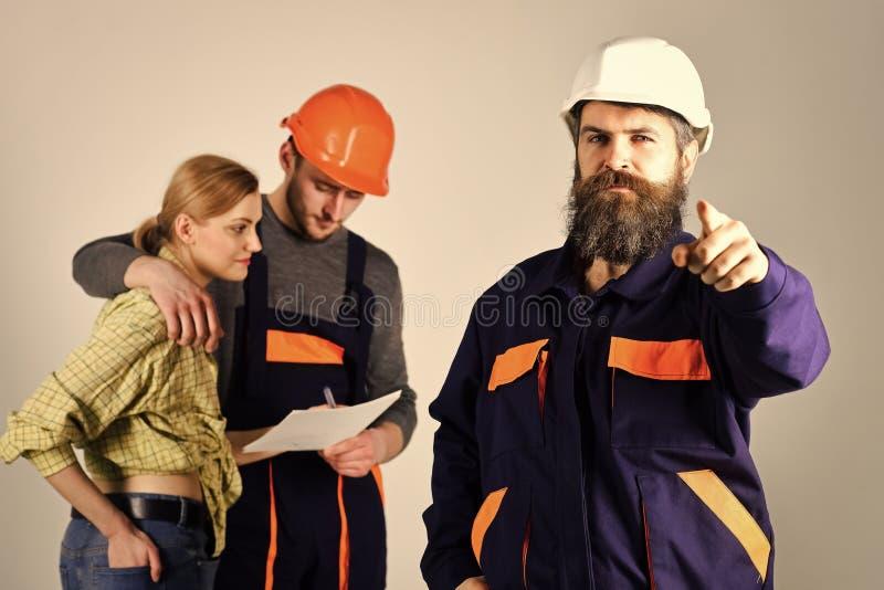 Concepto del reclutamiento Brigada de trabajadores, de constructores en cascos, de reparadores y de señora que discuten el contra imagen de archivo libre de regalías