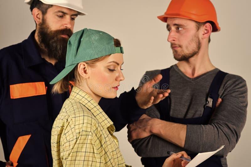 Concepto del reclutamiento Brigada de trabajadores, de constructores en cascos, de reparadores y de señora que discuten el contra fotografía de archivo